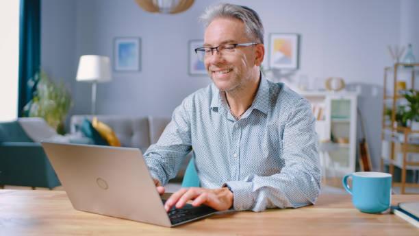 잘 생긴 중년 남자는 아늑하고 세련된 거실에서 자신의 책상에 앉아있는 동안 노트북 컴퓨터를 사용합니다. 행복한 성공적인 남자는 집에서 컴퓨터에서 작동합니다. - 한 명의 성년 남자만 뉴스 사진 이미지
