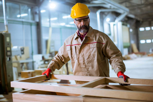 Handsome middle aged worker working in the furniture factory stock photo