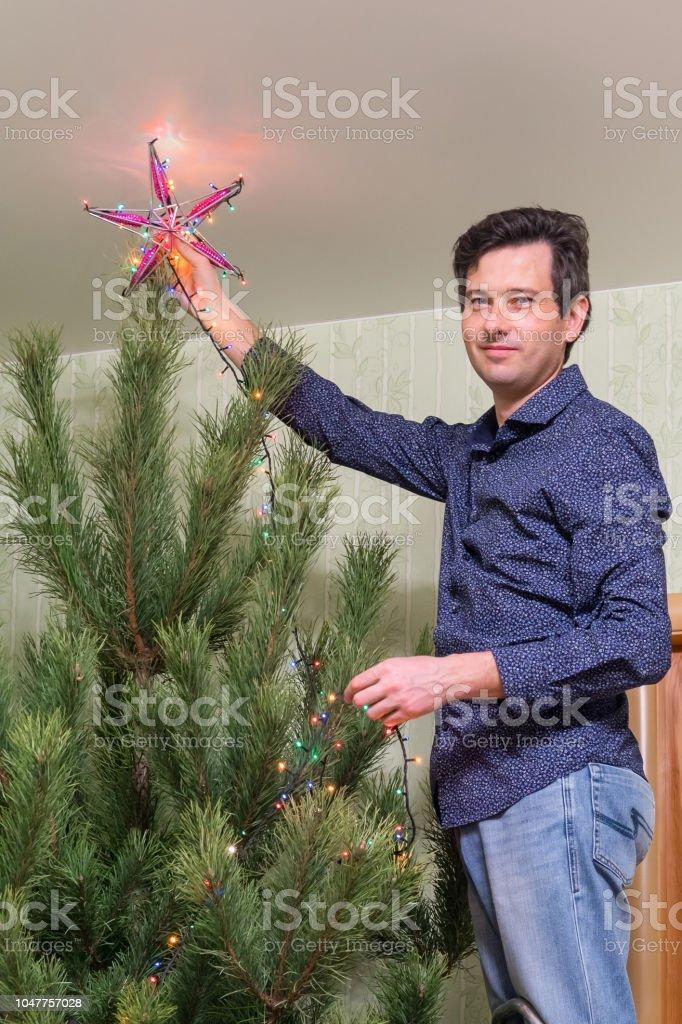 Warum Schmückt Man Den Weihnachtsbaum.Hübscher Mann Mittleren Alters Schmückt Einen Weihnachtsbaum Mit