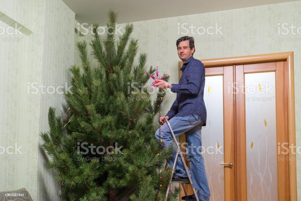 Warum Schmückt Man Den Weihnachtsbaum.Hübscher Mann Mittleren Alters Schmückt Einen Weihnachtsbaum Mit Stern Stockfoto Und Mehr Bilder Von Baum