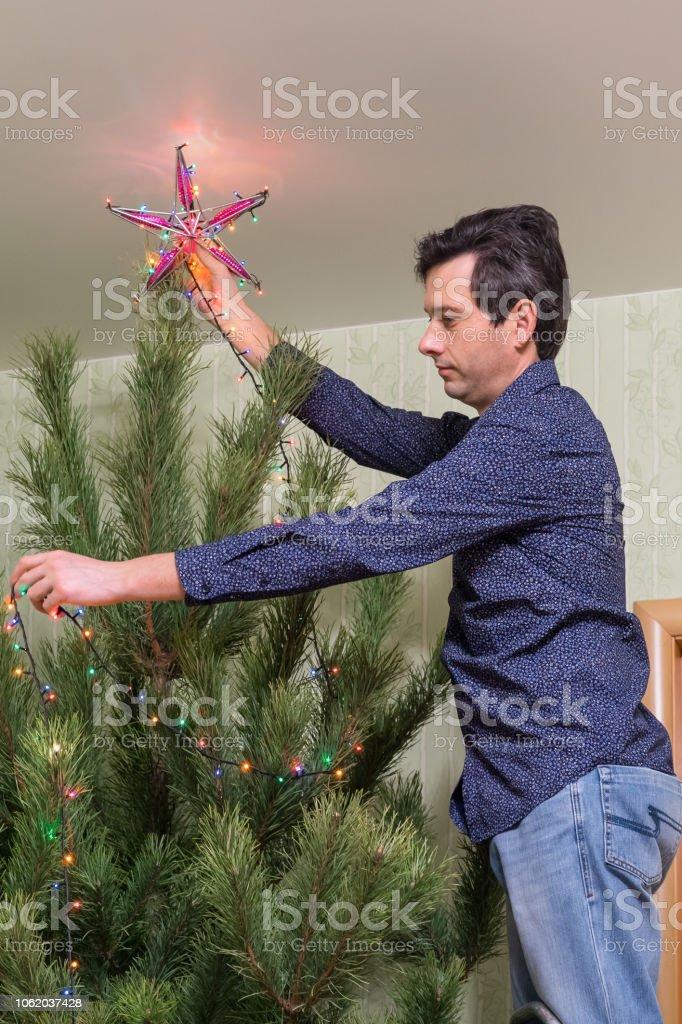 Wer Schmückt Den Weihnachtsbaum.Hübscher Mann Mittleren Alters Schmückt Einen Weihnachtsbaum Mit