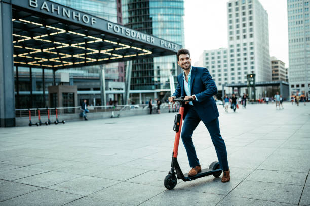 handsome millennial businessman on electric scooter going to work - monopattino elettrico foto e immagini stock