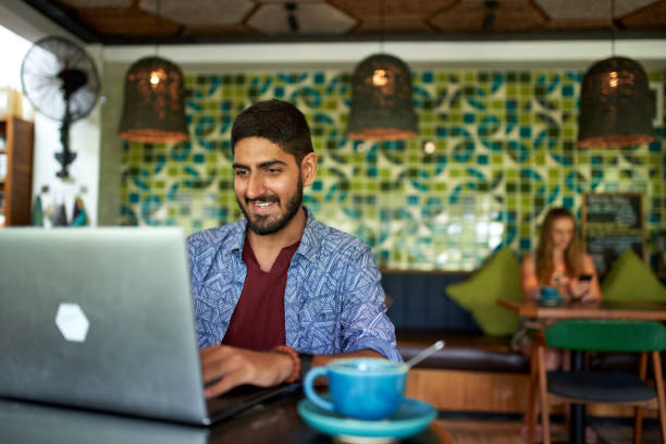 Handsome millennial indian man working in trendy coworking space cafe on laptop drinking organic fair-trade cappuccino stock photo