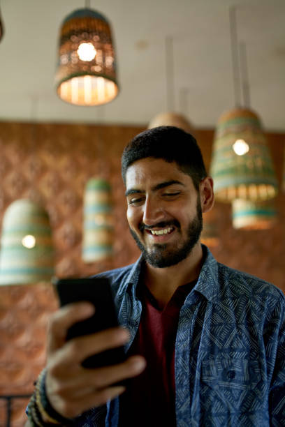 Handsome millennial man with beard using smartphone for video call in organic bohemian cafe stock photo