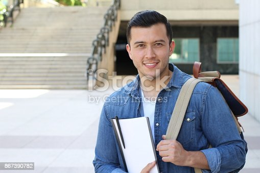 istock Handsome mixed race person heading to school 867390782