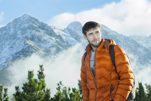 istock Handsome mountaineer posing at astonishing snowy rocky landscape background 518560534
