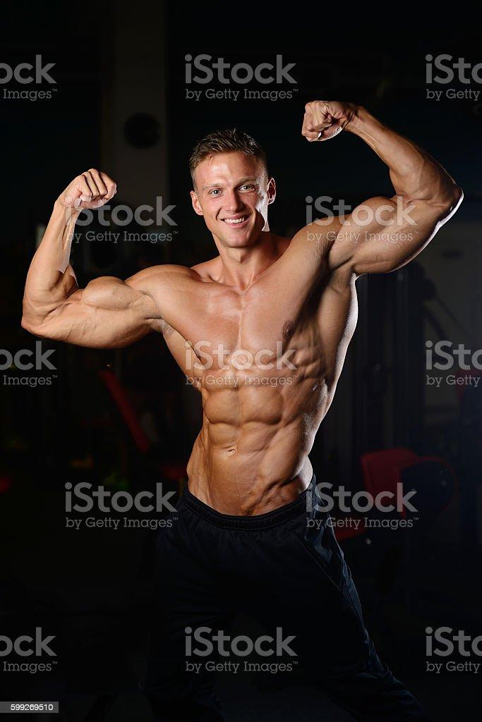 Foto de Handsome Muscular Bodybuilder Man Doing Exercises In