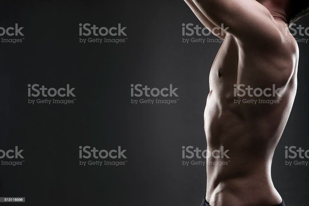 Handsome muscular bodybuilder posing on gray background stock photo