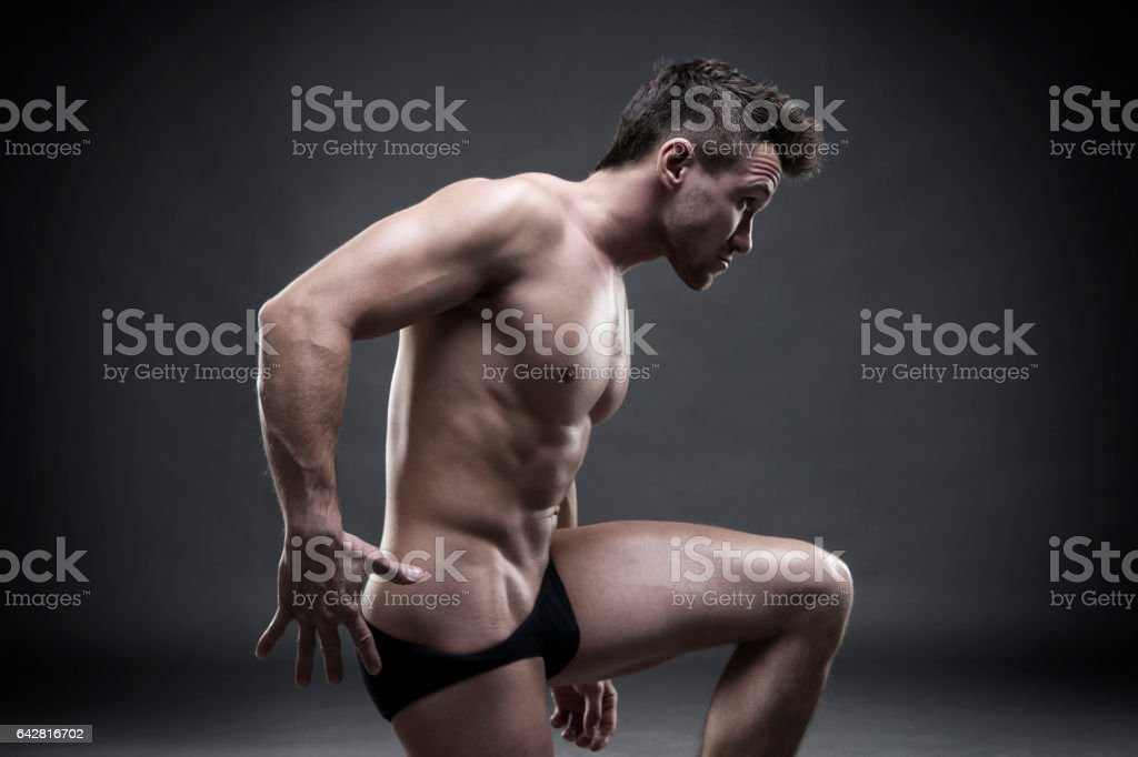 Handsome muscular bodybuilder posing on gray background, side view stock photo
