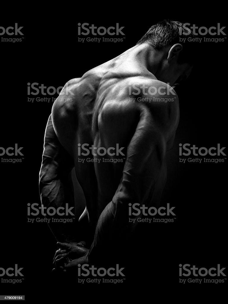 Handsome muscular bodybuilder turned back stock photo