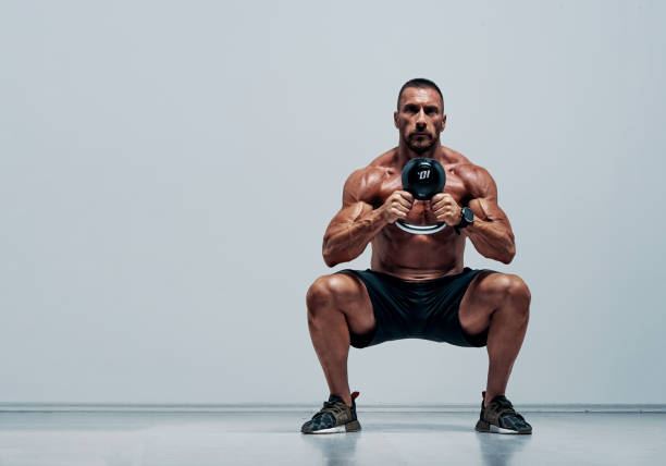 Handsome Muscular , Cross Training Athlete Doing Squats With Kettlebell stock photo