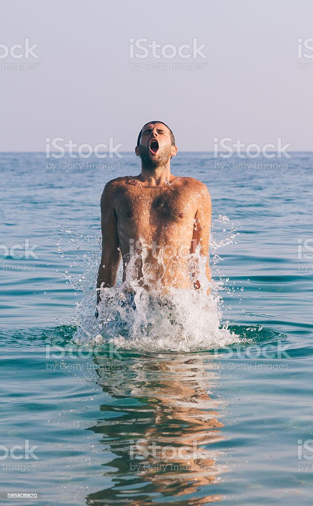 Handsome muscular guy jumping from water stock photo