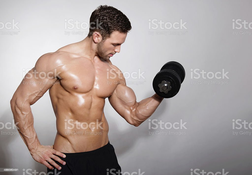 handsome muscular man handsome mucular man with dumbbell on grey background Abdomen Stock Photo