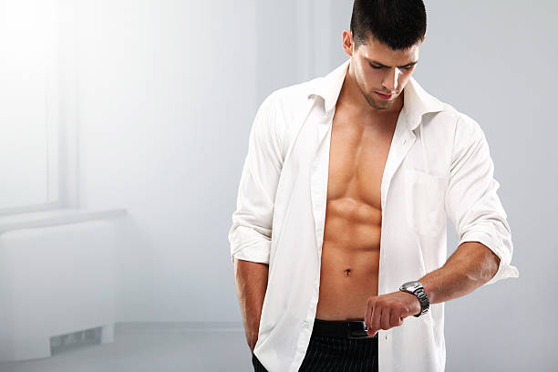 Handsome muscular man with a wristwatch. Handsome guy wearing unbuttoned white shirt and looking at his wristwatch. fully unbuttoned stock pictures, royalty-free photos & images