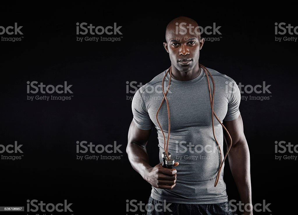 Handsome muscular man with jumping rope stock photo