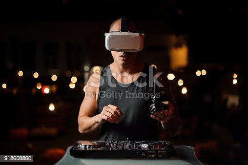 687096686 istock photo Handsome muscular nightclub DJ in night vision glasses 918608860