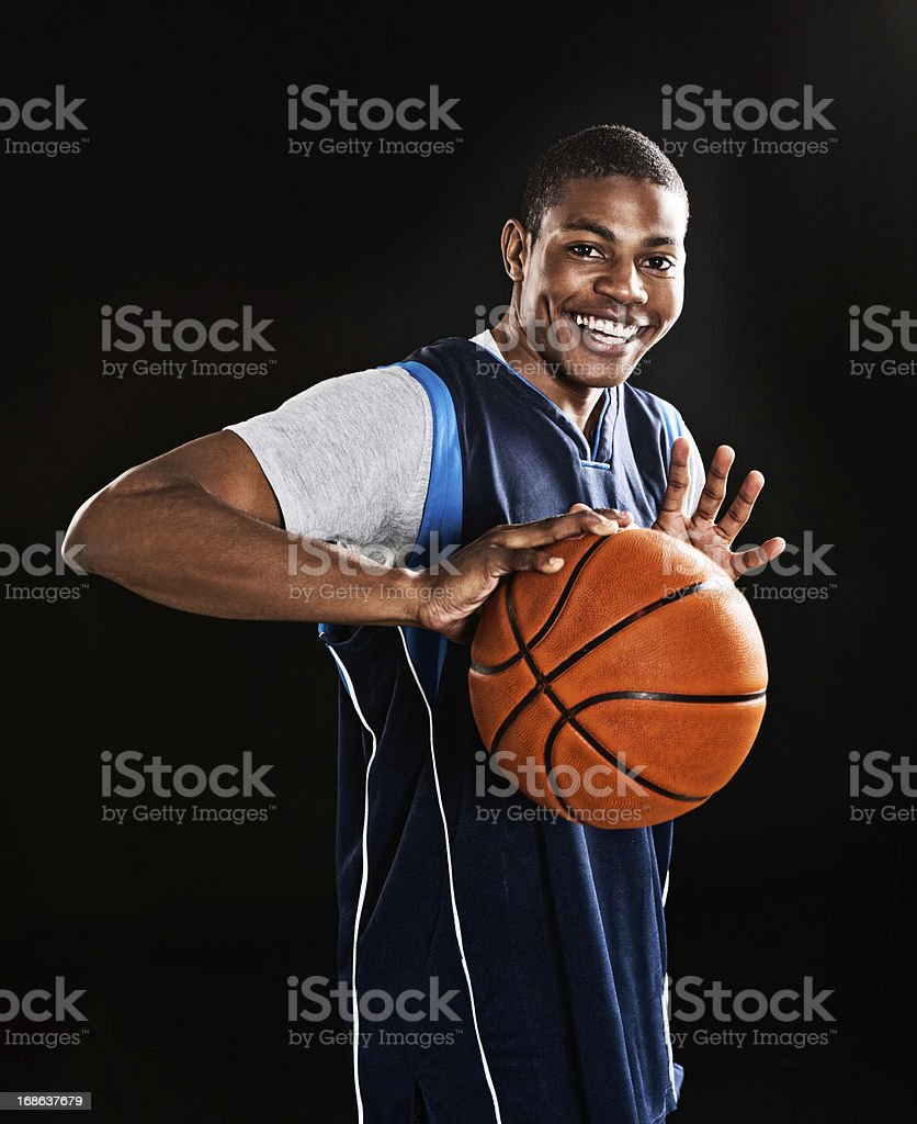 Handsome, muscular young basketball player smilingly prepares to play royalty-free stock photo