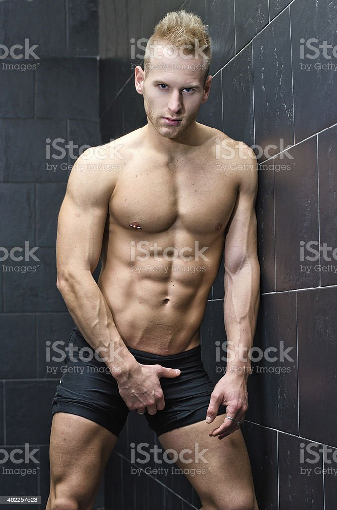 Handsome, muscular young man shirtless leaning against tiled wall royalty-free stock photo