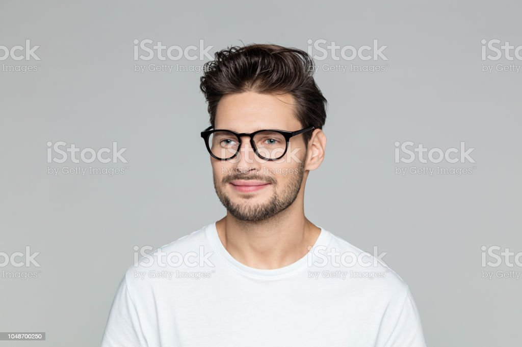 Handsome nerd on grey background Close up portrait of happy young man with beard wearing eyeglasses looking away against grey background 25-29 Years Stock Photo