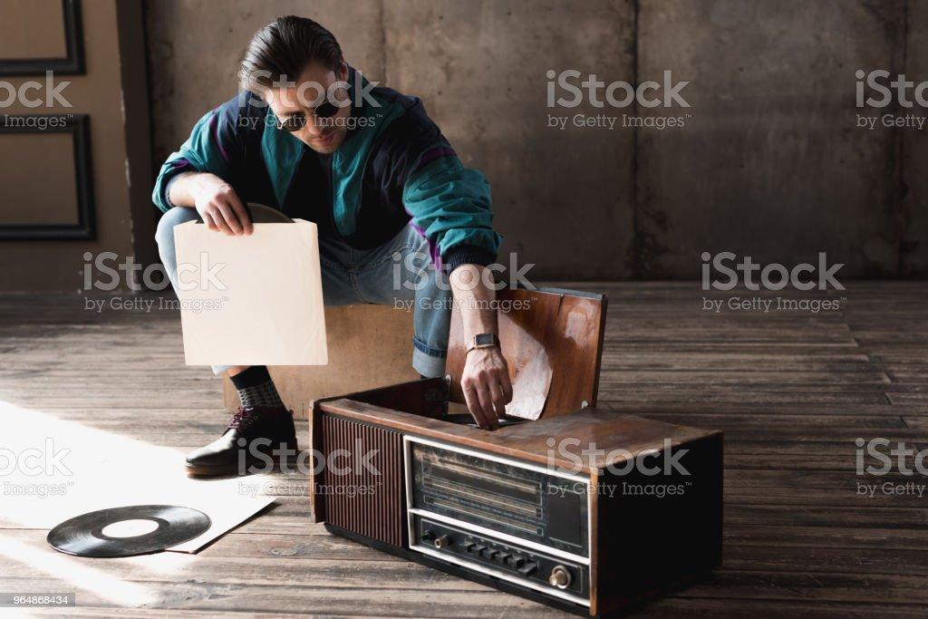 英俊的懷舊男子在老式 windcheater 與乙烯唱片播放機 - 免版稅一個人圖庫照片