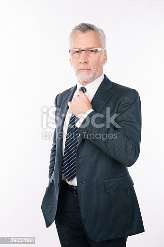 istock handsome old businessman in a business suit on a white background 1139032860