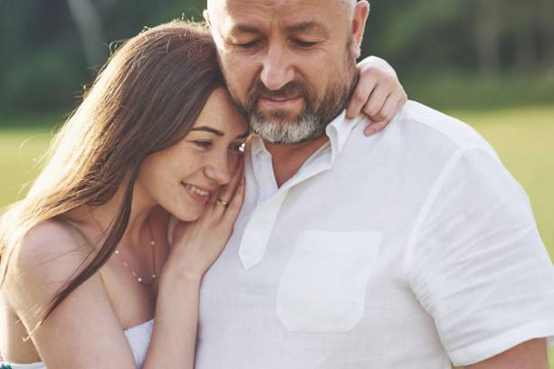 Hübscher alter Mann und schöne junge Mädchen umarmen, Tochter und ihr alter Vater verbringen Zeit zusammen im Freien – Foto