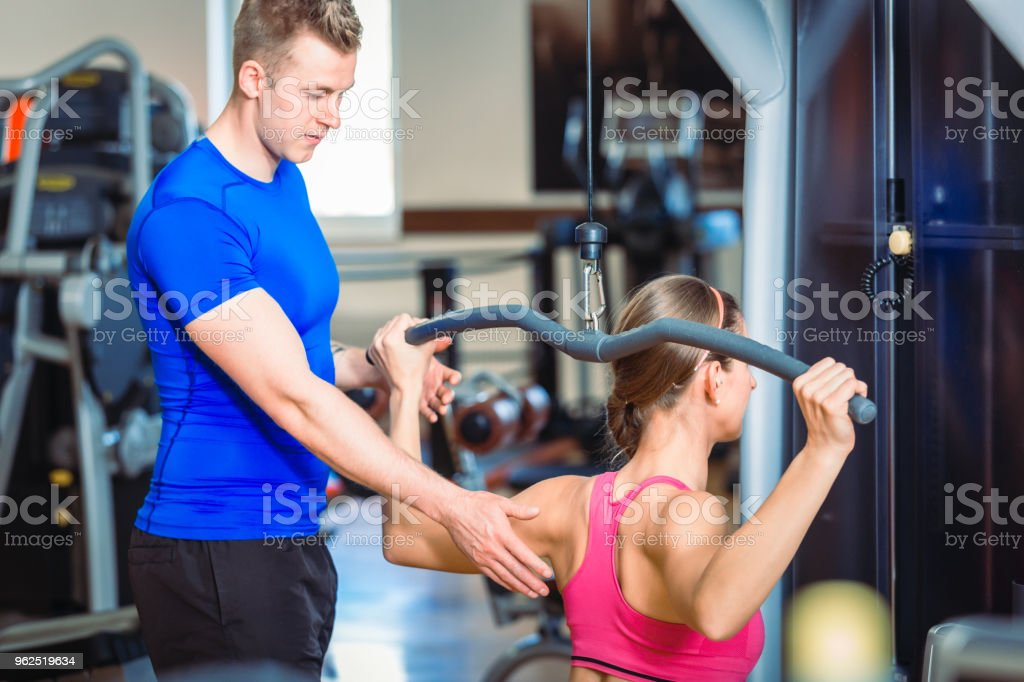 Handsome personal trainer guiding a beautiful woman at a modern fitness club - Royalty-free Adult Stock Photo