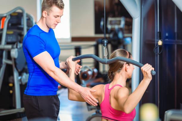 Gut aussehend persönlicher Trainer führt eine schöne Frau in einem modernen Fitnessclub – Foto