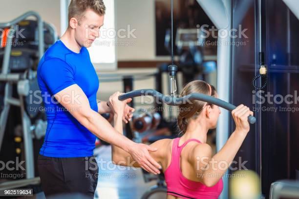 Foto de Treinador Pessoal Bonito Guiando Uma Bela Mulher Em Um Clube De Fitness Moderno e mais fotos de stock de Academia de ginástica