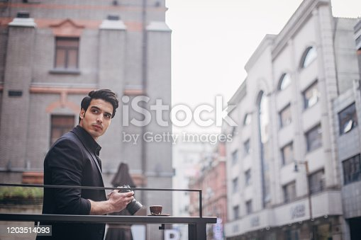 Handsome, elegant man taking photos with digital photo camera, drinking espresso.