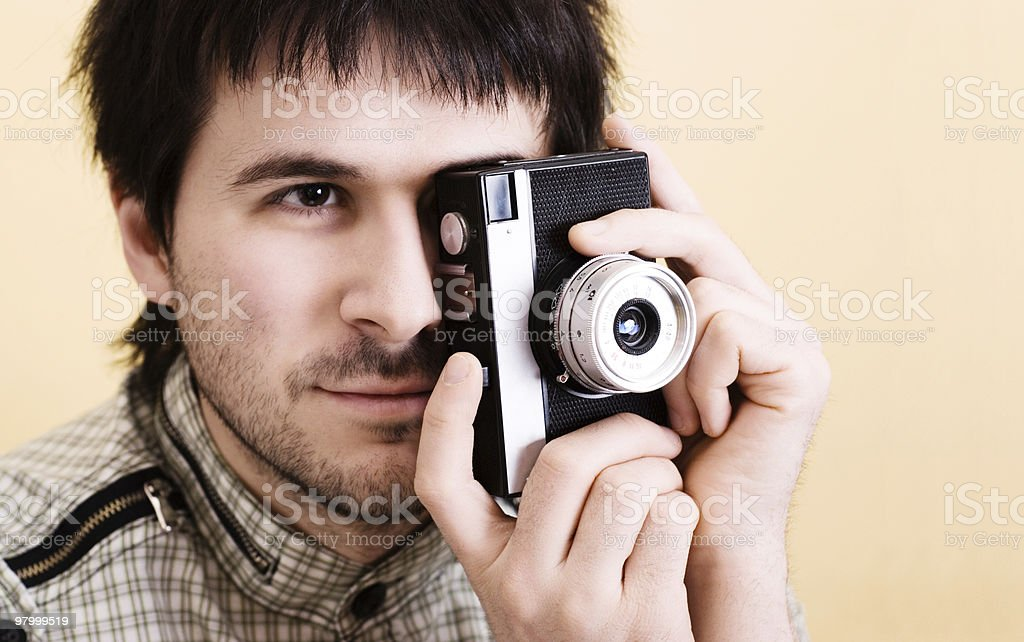 Handsome photographer photographing using retro camera. Copy space royalty-free stock photo