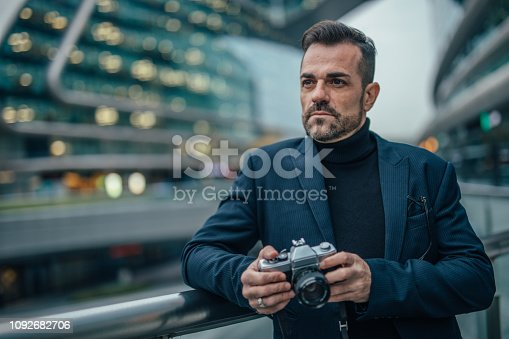 One man, handsome mature artist, holding photographic camera outdoors in city.