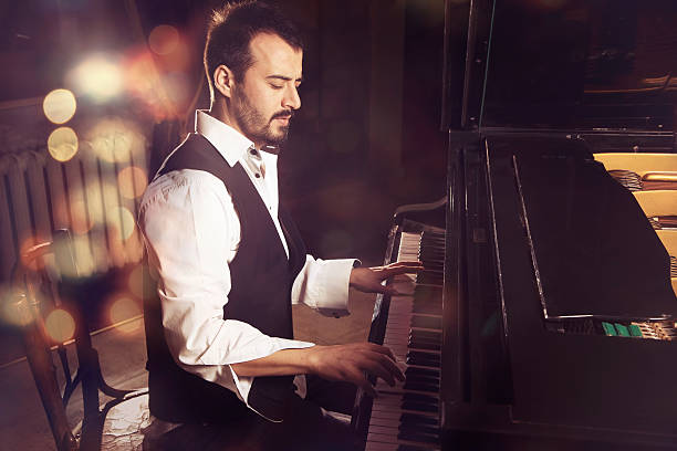 handsome piano player The handsome man playing the piano pianist stock pictures, royalty-free photos & images