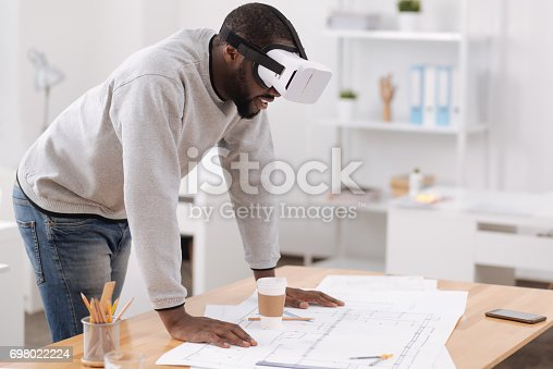 istock Handsome pleasant man studying the drawing 698022224
