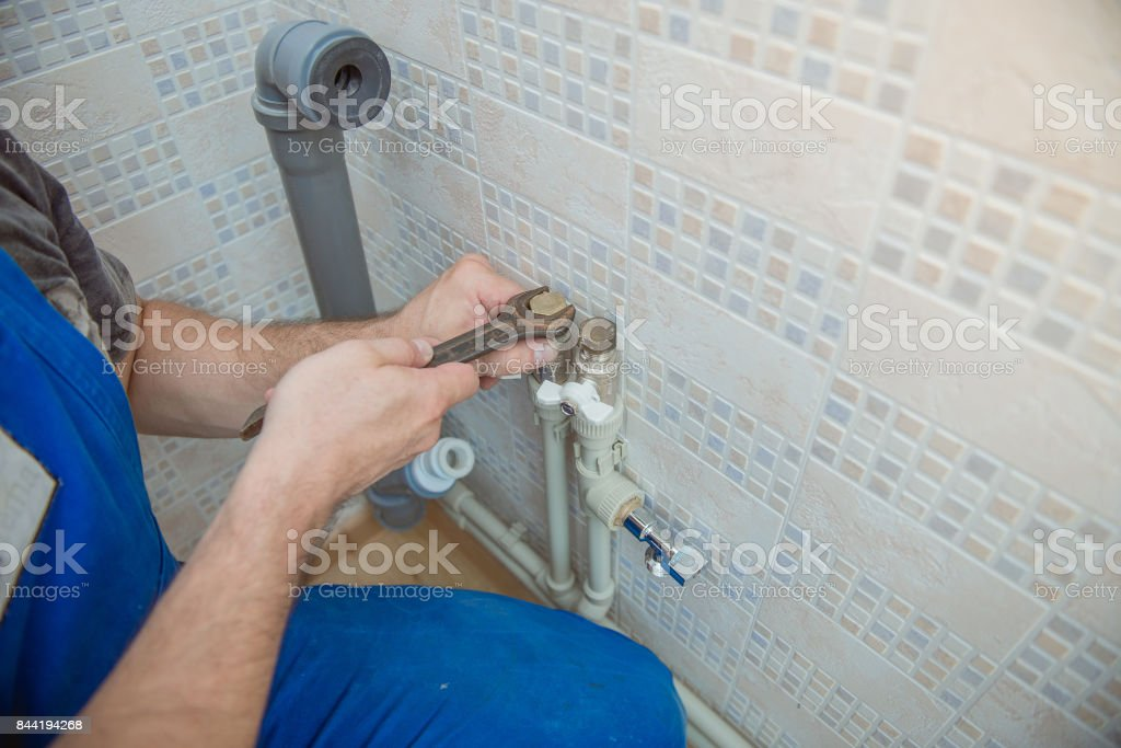 Handsome plumber replacing faucet in kitchen stock photo