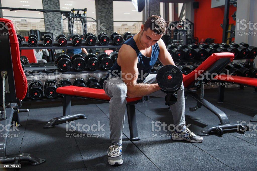 Homem bonito poder Atlético formação bombeamento músculos com haltere - foto de acervo