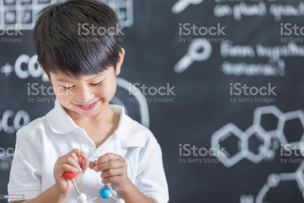 Cheerful Asian preschool age boy holds an atomic structure model. He...