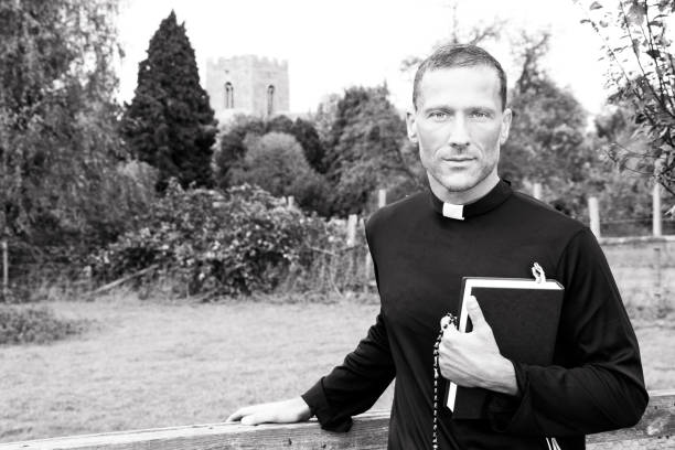 Handsome priest standing next to country gate while holding his bible with church and field in background stock photo