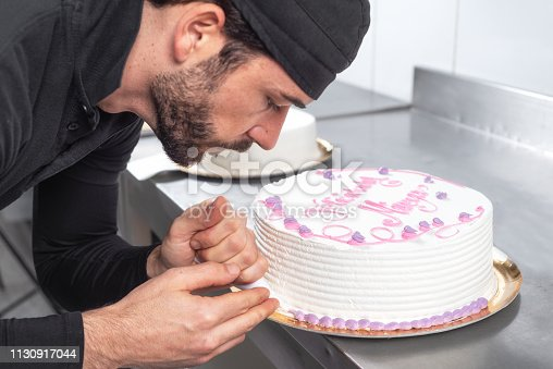 Handsome professional confectioner making a delicious cake in the pastry shop .
