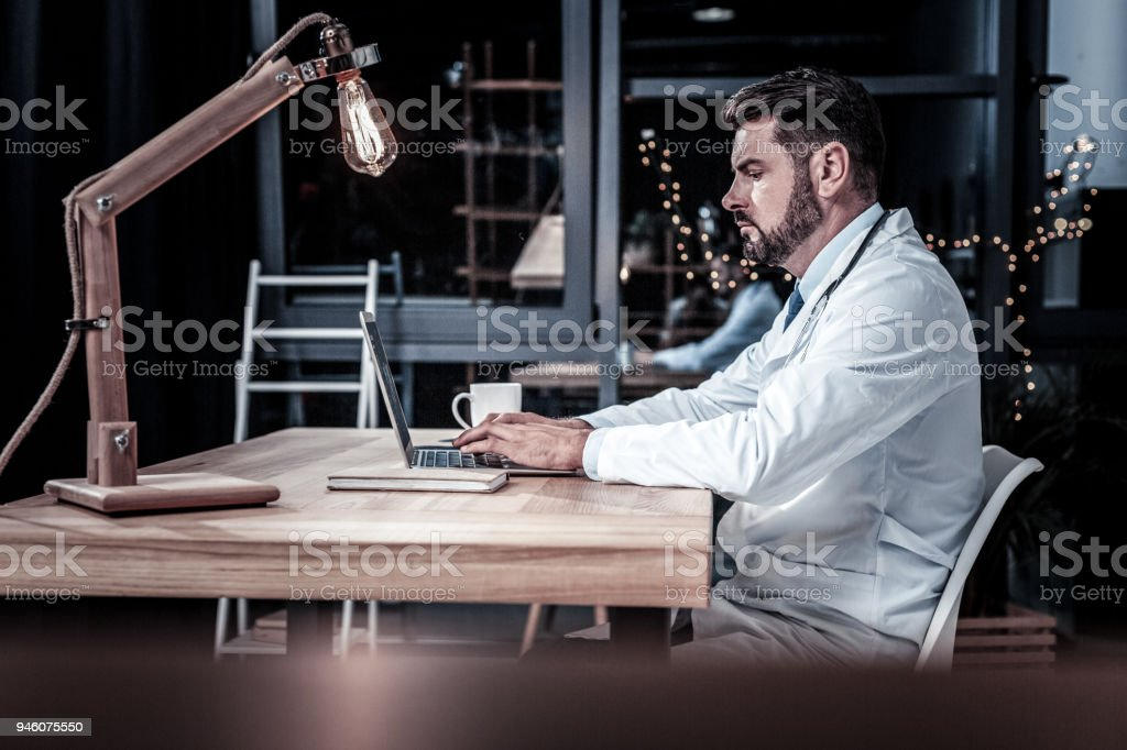 Handsome qualified medic sitting and working. stock photo