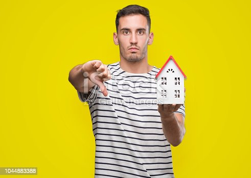 Handsome real estate agent holding a house with angry face, negative sign showing dislike with thumbs down, rejection concept