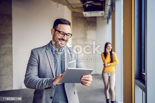 istock Handsome real estate agent in suit standing in building in construction process and using tablet for make appointment with customers. In background his colleague standing and talking on the phone. 1193382198