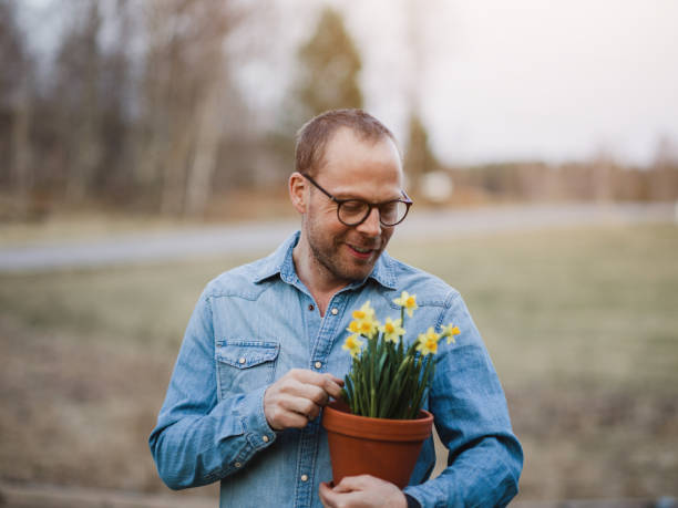 Handsome real man outdoors in nature in spring with daffodils stock photo