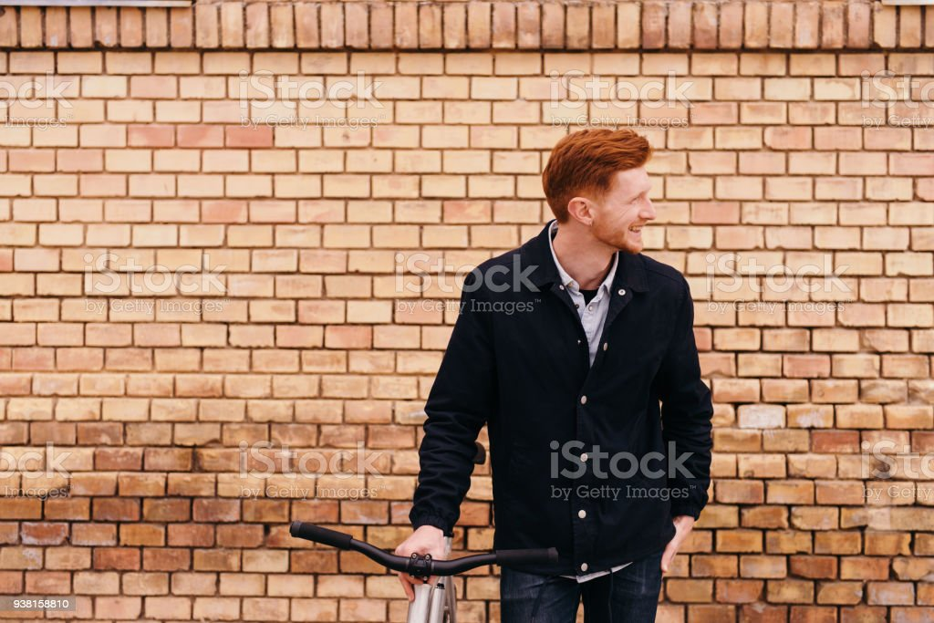 Handsome red hair young hipster man standing with his bicycle over brick wall stock photo