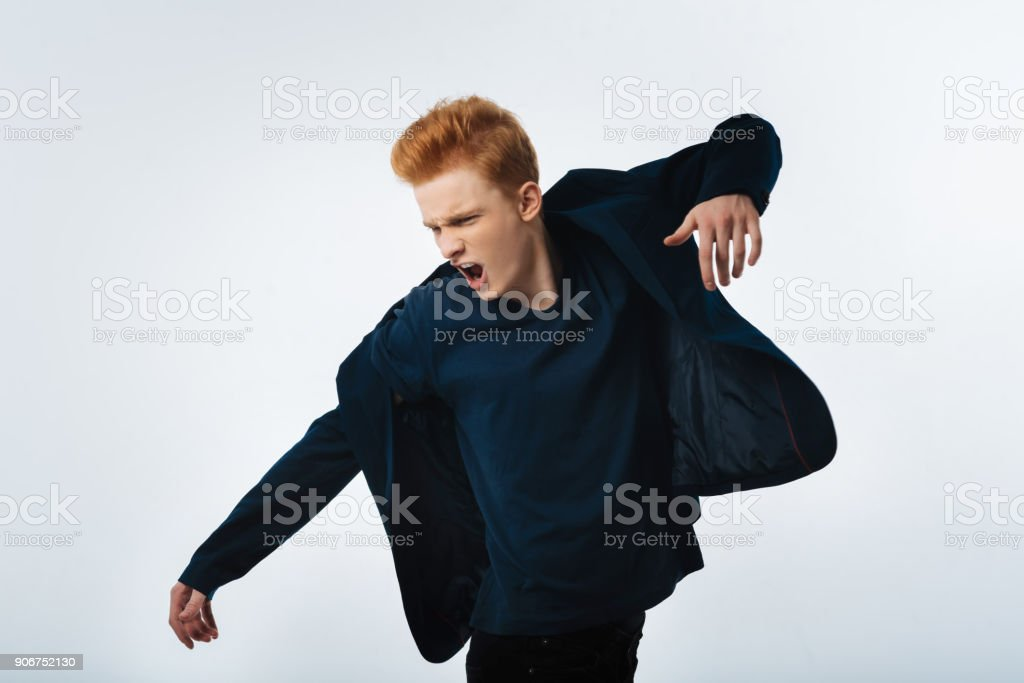 Handsome red-headed young man shouting stock photo