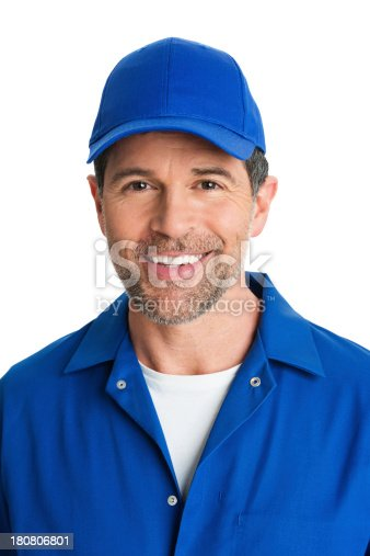 Close-up of handsome mature repairman in blue uniform smiling against white background