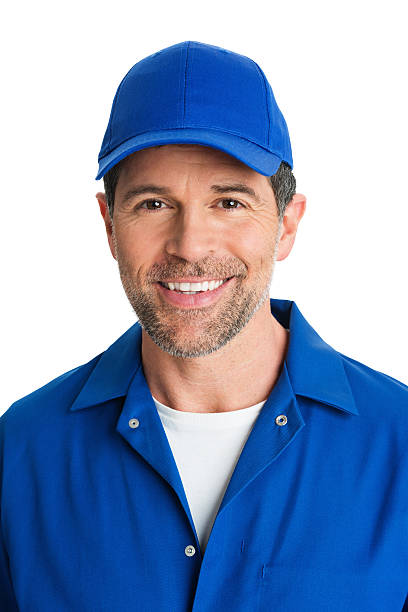 Handsome Repairman In Blue Uniform Smiling Close-up of handsome mature repairman in blue uniform smiling against white background baseball cap stock pictures, royalty-free photos & images