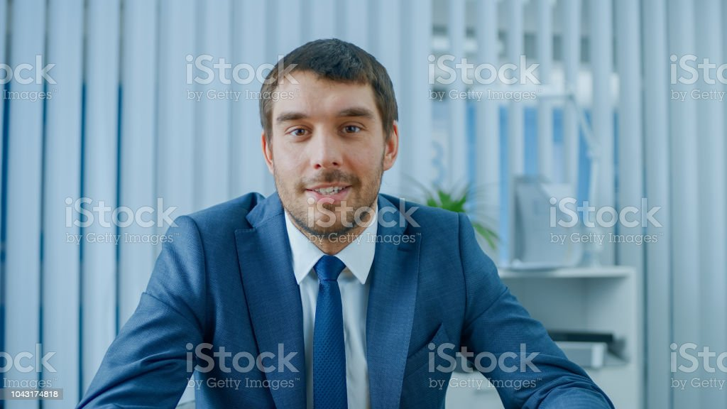 Handsome Respectable Businessman Sitting at His Desk in Office, Looking into the Camera. stock photo