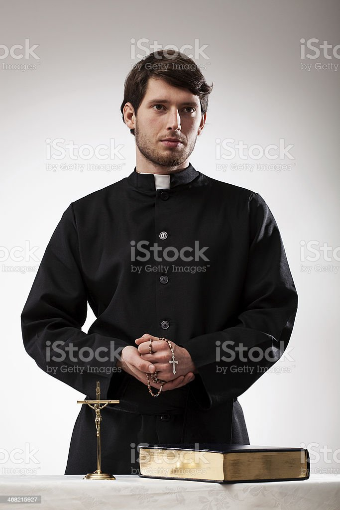 Handsome reverend with crucifix and the Bible stock photo