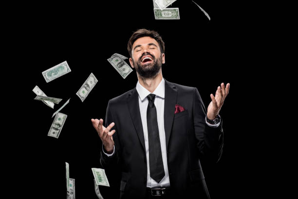 handsome rich excited businessman throwing dollar banknotes, isolated on black - money black background stock photos and pictures